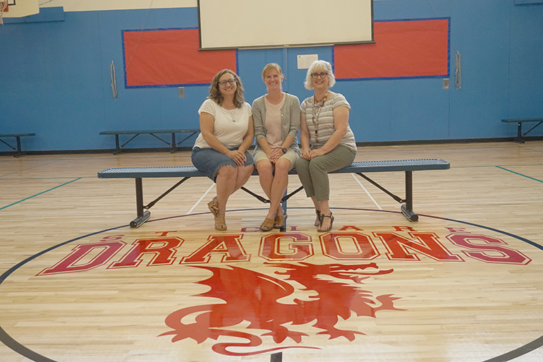 Angela Romanaggi, Jessica Montgomery and Paige Sturges — teachers at St. Clare School —  pose behind the new logo on the St. Clare gym floor. (Courtesy St. Clare School)
