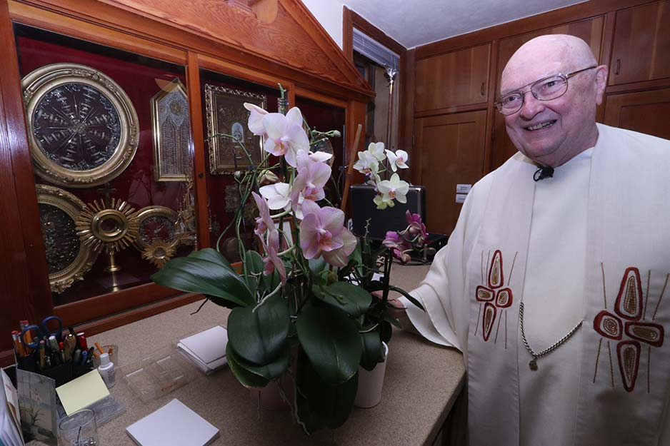 "Holy Cross Father Richard Berg has taken in failing orchids and revived them by placing them in the sacristy window in the Mary's Woods chapel — also near a collection of relics. ""It's the light, not me,"" the priest says. (Ed Langlois/Catholic Sentinel)"