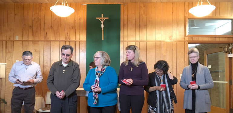 Juan Urias OFS, formation director of St. Clare Fraternity of the Secular Franciscans, stands beside David Wickham, Nancy Anderson, Julie McCauley, Manuela Wickham and Annie Lukasik, all receiving tau crosses as an outward sign of their Secular Franciscan identity. The men and women entered the candidacy stage of formation Nov. 18. (Courtesy Evelyn Brush OFS)