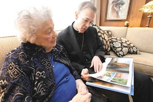Joyce Sample and her son, Archbishop Alexander Sample, look over a book about Oregon just before leaving Marquette, Michigan. (Ed Langlois/Catholic Sentinel)