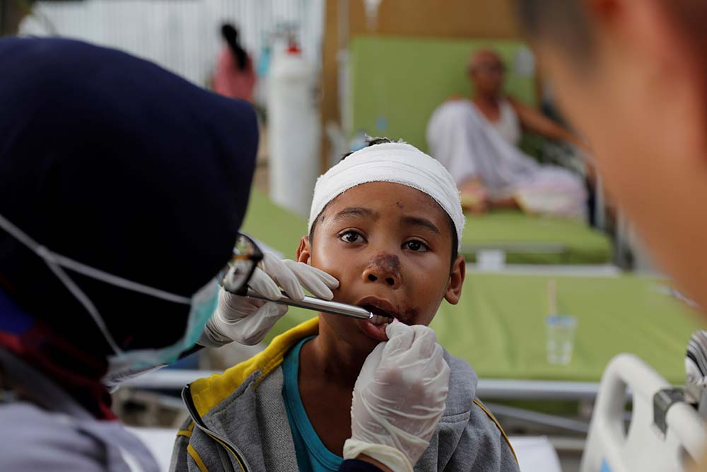 aramedics treat a young earthquake survivor Aug. 7 at Tanjung hospital on Lombok, Indonesia. At least 105 people have been confirmed dead after the magnitude 6.9 earthquake Aug. 5, a week after another powerful quake killed more than a dozen people. (CNS photo/Beawiharta, Reuters)