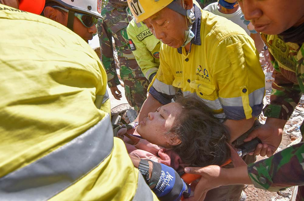 Rescue workers and soldiers carry a woman Aug. 7, who survived after being trapped in rubble following an earthquake on Lombok, Indonesia.