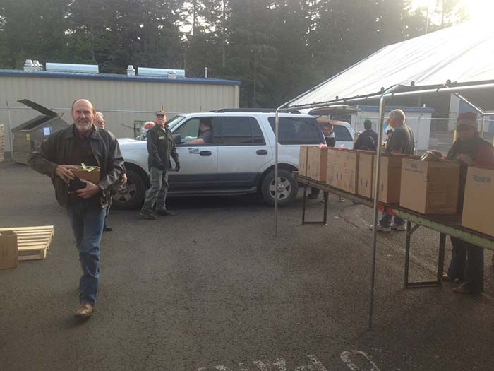 Cars drive past at their appointed time to receive food boxes in North Bend. Volunteers from all sectors of society on the South coast cooperate in the annual Christmas feeding program. (Courtesy Knights of Columbus Council 1261)