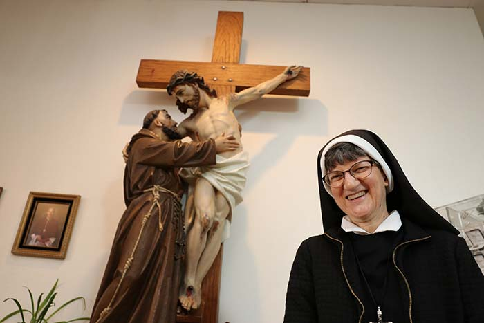 "Sr. Louismarie Premazzi stands beside a statue at Our Lady of Peace Retreat in Beaverton — St. Francis helping Jesus down from the cross. The former cloistered nun entered the Franciscan Missionary Sisters of Our Lady of Sorrows in April. ""Franciscan is my true calling. It's been that way from the start,"" she says. ""It just took some time."" (Ed Langlois/Catholic Sentinel)"