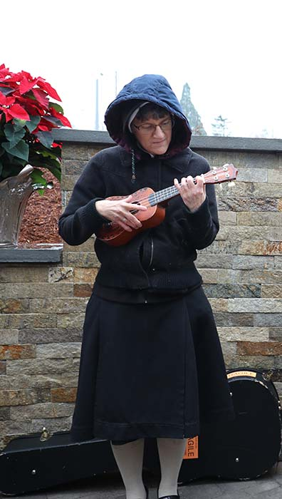 Sr. Louismarie Premazzi plays ukulele during the dedication of a new Marian prayer garden Dec. 8 at Our Lady of Peace Retreat. (Ed Langlois/Catholic Sentinel)