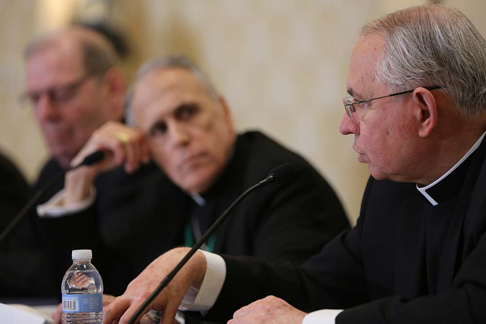 Archbishop Jose H. Gomez of Los Angeles, vice president of the U.S. Conference of Catholic Bishops, speaks during a news conference on the first day of the spring general assembly of the USCCB in Baltimore June 11, 2019. Also pictured are Bishop Robert P. Deeley of Portland, Maine, and Cardinal Daniel N. DiNardo of Galveston-Houston, president of the USCCB. (CNS photo/Bob Roller)