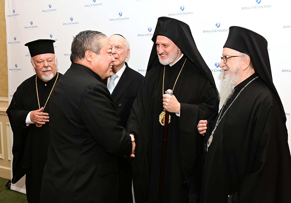 Archbishop Bernardito Auza, the Vatican's permanent observer to the U.N., greets Archbishop Elpidophoros of America following his enthronement as the seventh archbishop of the Greek Orthodox Archdiocese of America at the Cathedral of the Holy Trinity in the Manhattan borough of New York City June 22, 2019. Also pictured are retired Metropolitan Avgoustinos of Germany, Rabbi Arthur Schneier of New York City's Park East Synagogue and Archbishop Demetrios, who headed the Greek Orthodox Archdiocese of America from 1999 until 2019. (CNS photo/Dimitrois Panagos, courtesy GOA)