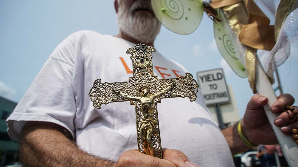 A pro-life supporter holds a crucifix outside of a Planned Parenthood facility in St. Louis May 31. A new Public Religion Research Institute survey of more than 54,000 Americans released Aug. 13, shows 54% of Americans believe abortion should be legal in all or most cases, while 40% believe it should be illegal in most or all cases, reflecting attitudes little changed from a 2014 survey. But researchers also detected movement in many demographic groups, Catholics included. (CNS photo/Lawrence Bryant, Reuters)