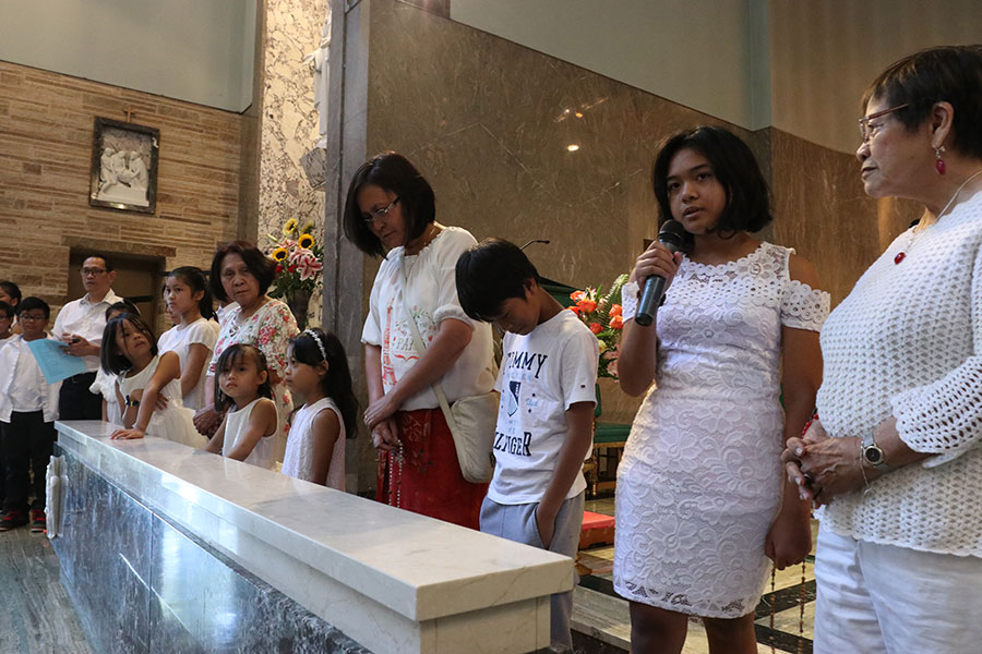 Thela Pesquera, holding the microphone, and other Filipino American children lead a rosary before the annual Dambana Mass at The Grotto July 28. (Ed Langlois/Catholic Sentinel)