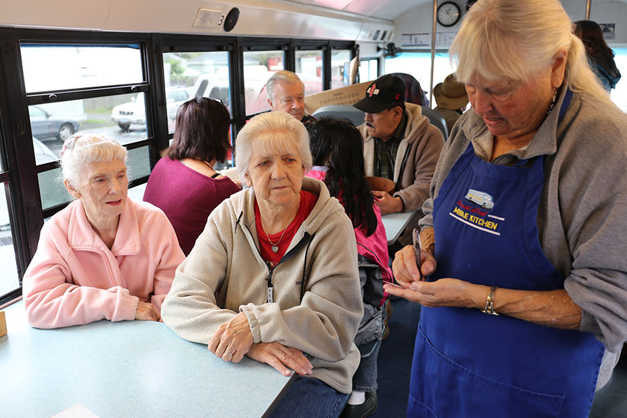 "Judy Ziegelmayer, former president of the St. Aloysius conference of St. Vincent de Paul and a current mobile kitchen volunteer, takes food orders from Betty McDaniel and Dolores Scastone. The cafe on wheels is ""an opportunity to get out of my little apartment and to visit with people,"" says McDaniel, who resides in a nearby senior living community. (Katie Scott/Catholic Sentinel)"