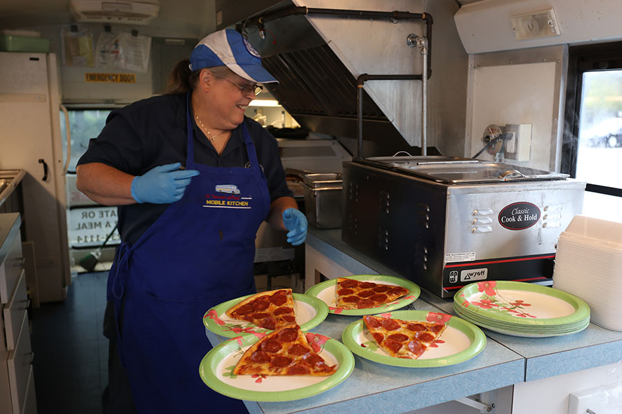 "Diana Day, a St. Vincent de Paul employee, plates slices of hot pizza in the St. Vincent de Paul mobile kitchen Sept. 17. Day, who also drives the bus, ""loves to help people,"" she says. (Katie Scott/Catholic Sentinel)"