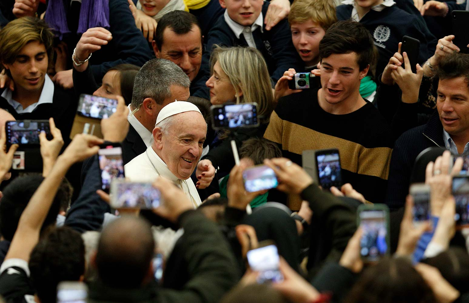 People capture images on their phones as Pope Francis arrives to lead his general audience in Paul VI hall at the Vatican Feb. 5. (CNS photo/Paul Haring)