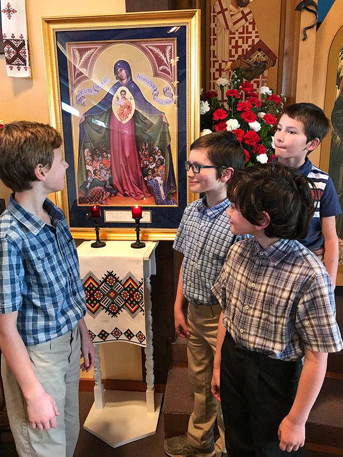 Malachai Whitaker, Andrew and Timothy May, Joaquin Baker learn about the plight of Christians gathered in prayer under Mary's mantle in the icon. (Courtesy Nativity of the Mother of God Ukrainian Parish)