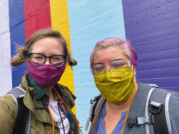 "Outreach team leader Marielle McKenna (in the red face cover) and Jennifer Lucena (in green face cover) pause as they walk to speak with people who are homeless in the St. Francis Parish area of inner Southeast Portland. The Housing Transition Program outreach staff go out in teams of two. ""The work we do is only because of the amazing team we have,"" said Lucena. (Courtesy MJ)"