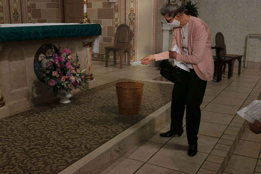 Cynthia Stanley drops a fire relief donation into a basket at Sacred Heart Parish Sept. 20. (Ed Langlois/Catholic Sentinel)