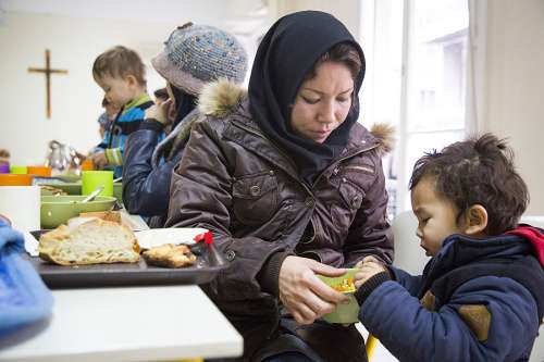 A mother and daughter eat at a refugee site in Athens, Greece. A similar ministry is about to open in Rome with the Vatican in charge. (CNA)