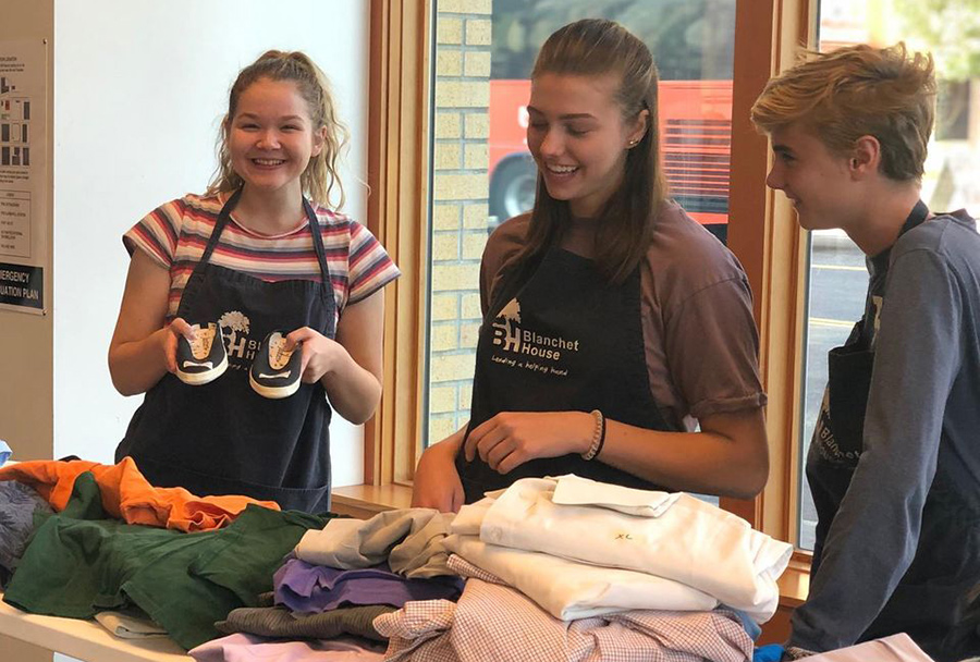 Chase Kerman (left) a junior at Jesuit High School, works in the clothing closet of Blanchet House last year. She is a new ambassador for the ministry.