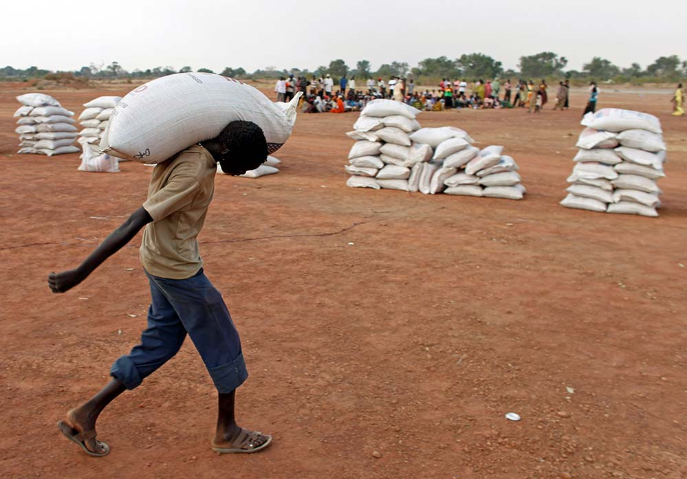 A man is pictured in a file photo carrying a sack of flour distributed by World Food Program in Aweil, South Sudan. The Nobel Committee has awarded the 2020 Nobel Peace Prize to the World Food Program. (CNS photo/Goran Tomasevic, Reuters)