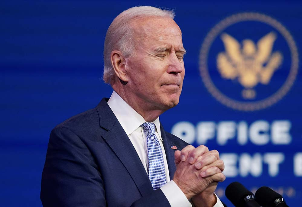 President-elect Joe Biden clasps his hands in prayer position during a news conference at his transition headquarters in Wilmington, Del., Jan. 6 as he addresses the protests taking place in and around the U.S. Capitol in Washington as the Congress held a joint session to certify the 2020 election results. (CNS photo/Kevin Lamarque, Reuters)
