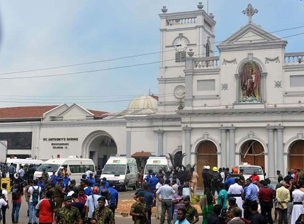 Ambulances are seen outside the church premises with gathered people and security personnel following a blast at St. Anthony's Shrine in Kochchikade, Colombo on April 21, 2019. (Credit: ISHARA S. K)