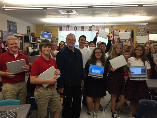 St. Agatha eighth graders show new laptops, blessed by Father Nathan Zodrow, the pastor. Observers laud the school's feeling of family.