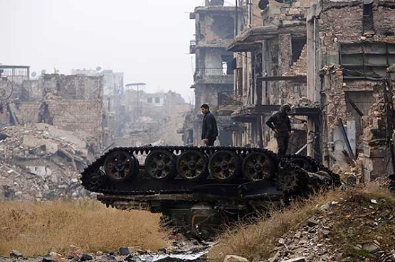 CNS photo/Omar Sanadiki, ReutersForces loyal to Syrian President Bashar Assad stand atop a damaged tank Dec. 13 in the destroyed government-controlled area of Aleppo.