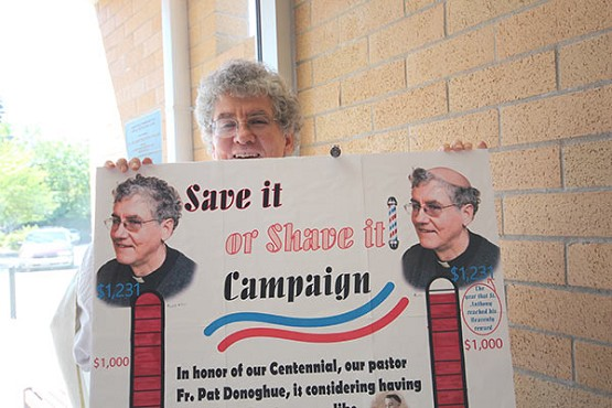 Ed Langlois/Catholic SentinelFr. Pat Donoghue peers over a poster made to promote a fundraising competition between those who wanted to see him shave his head like a medieval friar or preserve his curly locks. The save side barely won out.