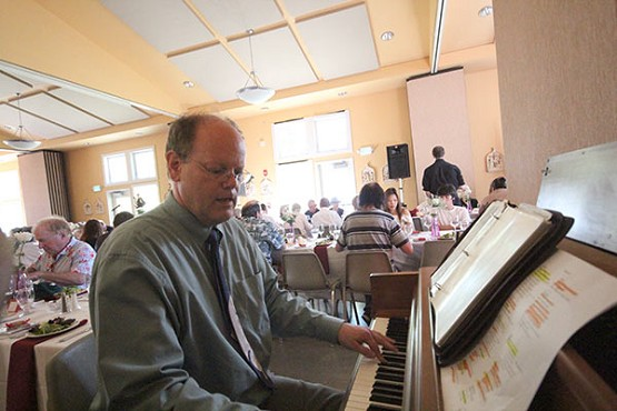 Theo Burke works the ivories as entertainment during the centennial banquet at St. Anthony Parish.