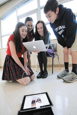 Erin Foley, Sofia Mercado, teacher Liane Rae and Hanjin Jacobs work on a science skit using an iPad at Cathedral School in Portland.