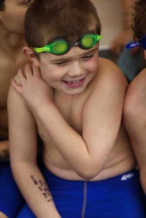 Giggles and goggles — A young swimmer, a Polliwog in CYO parlance, enjoys a moment poolside.