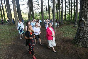 Pilgrims pray the rosary on path through woods in Crooked Finger.